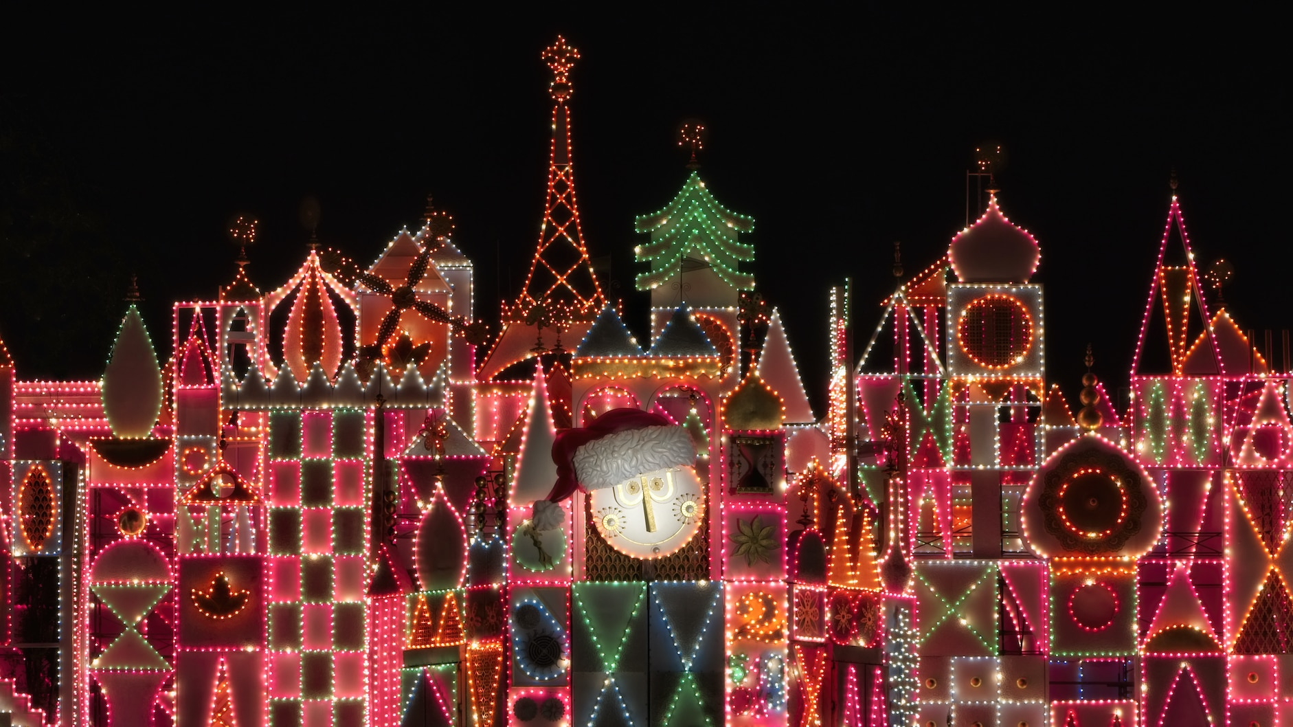"""Image of the exterior/clock tower lit up at night at the """"it's a small world"""" ride."""