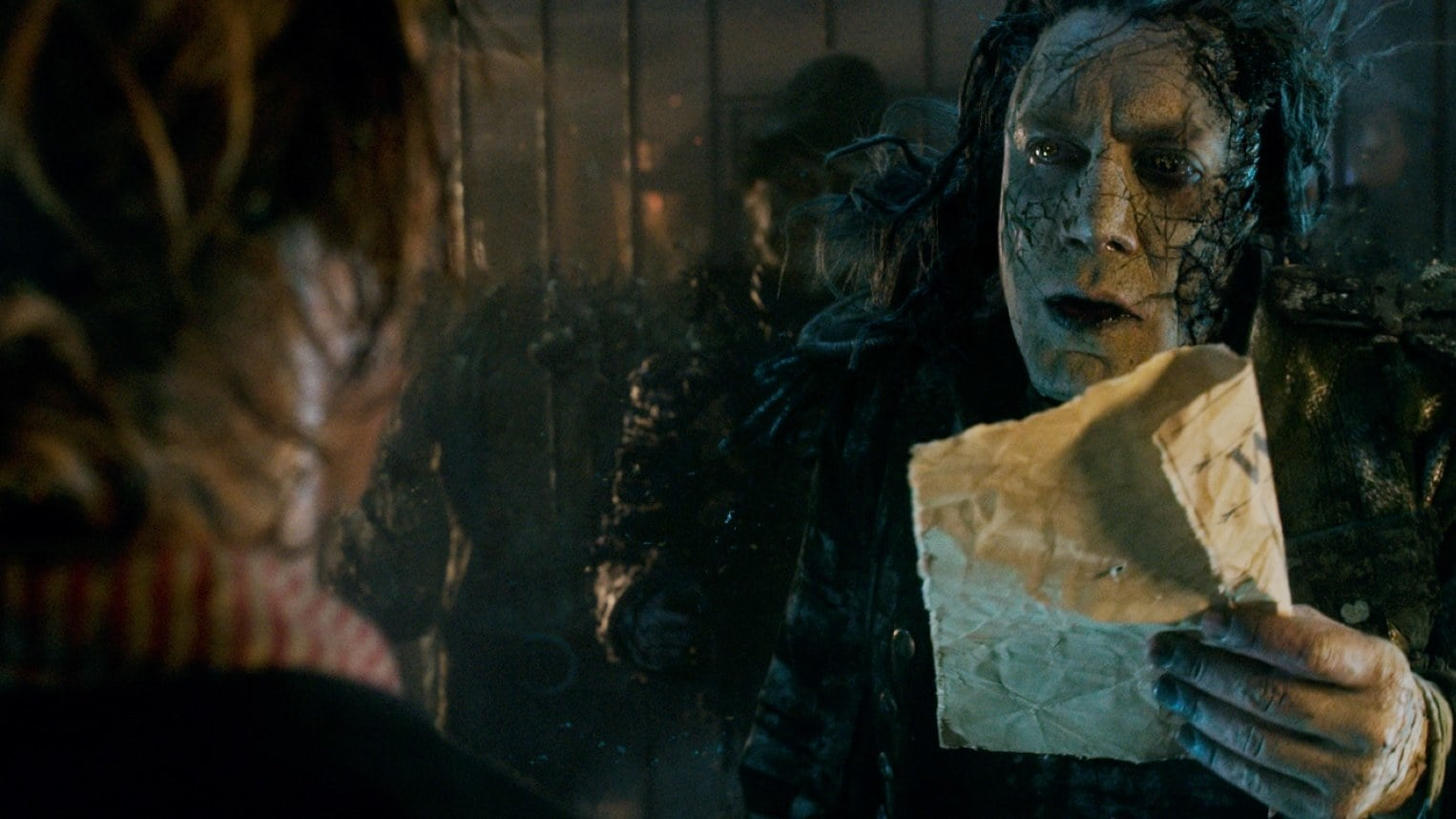 Captain Salazar, played by Javier Bardem, holding a crumpled piece of paper talking to another in the movie Pirates of the Caribbean: Dead Men Tell No Tales