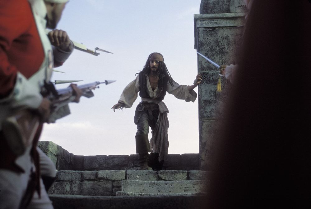 Actor Johnny Depp as Captain Jack Sparrow backed to a ledge by British soldiers