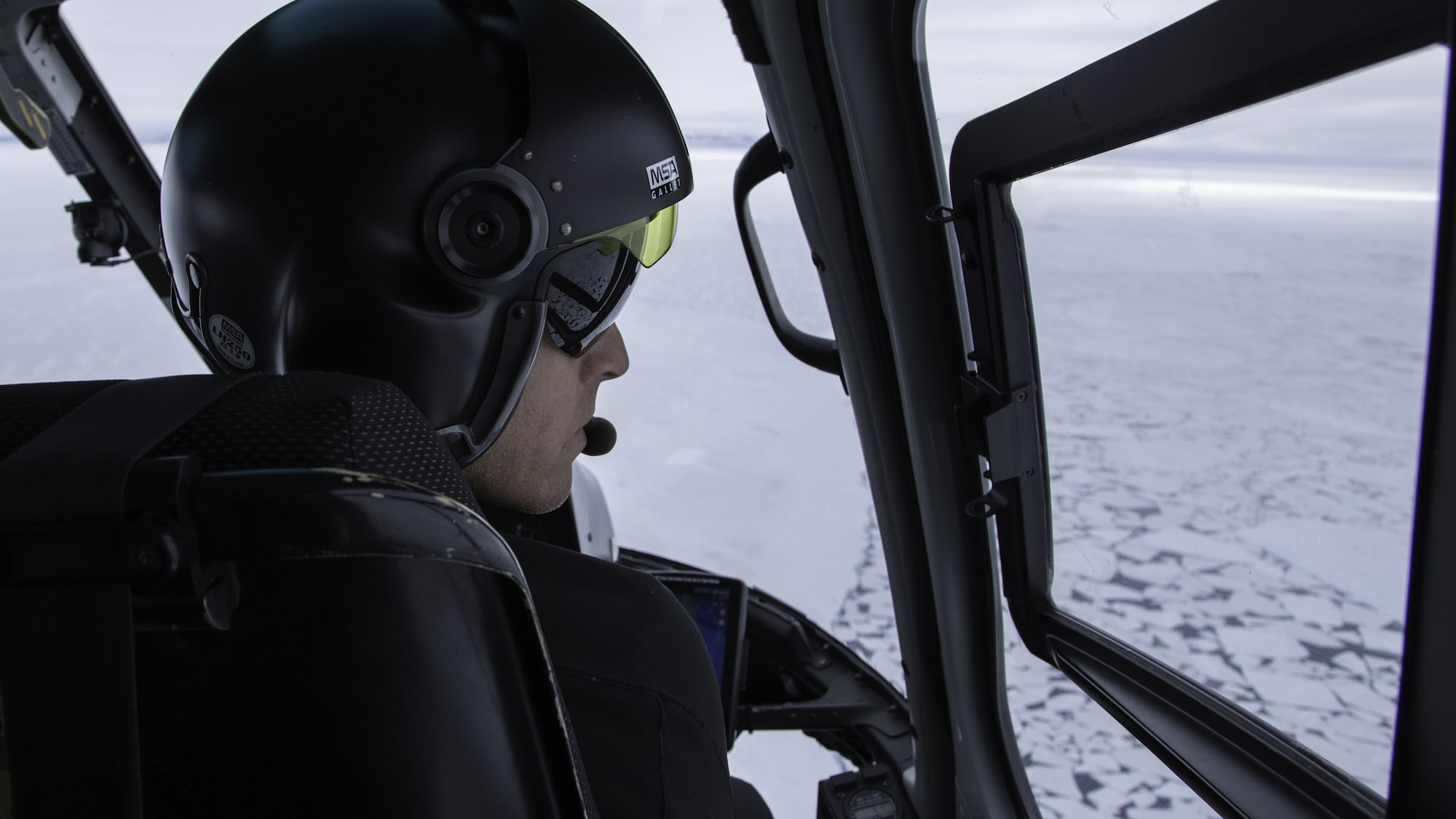 Pilot Paul Guarducci flies over broken sea ice in the Canadian Arctic. The Planet of the Whales team used a specialty rig on a helicopter to film narwhals and belugas from a distance - essential for capturing natural behavior. (National Geographic for Disney+/Sam LeGrys)