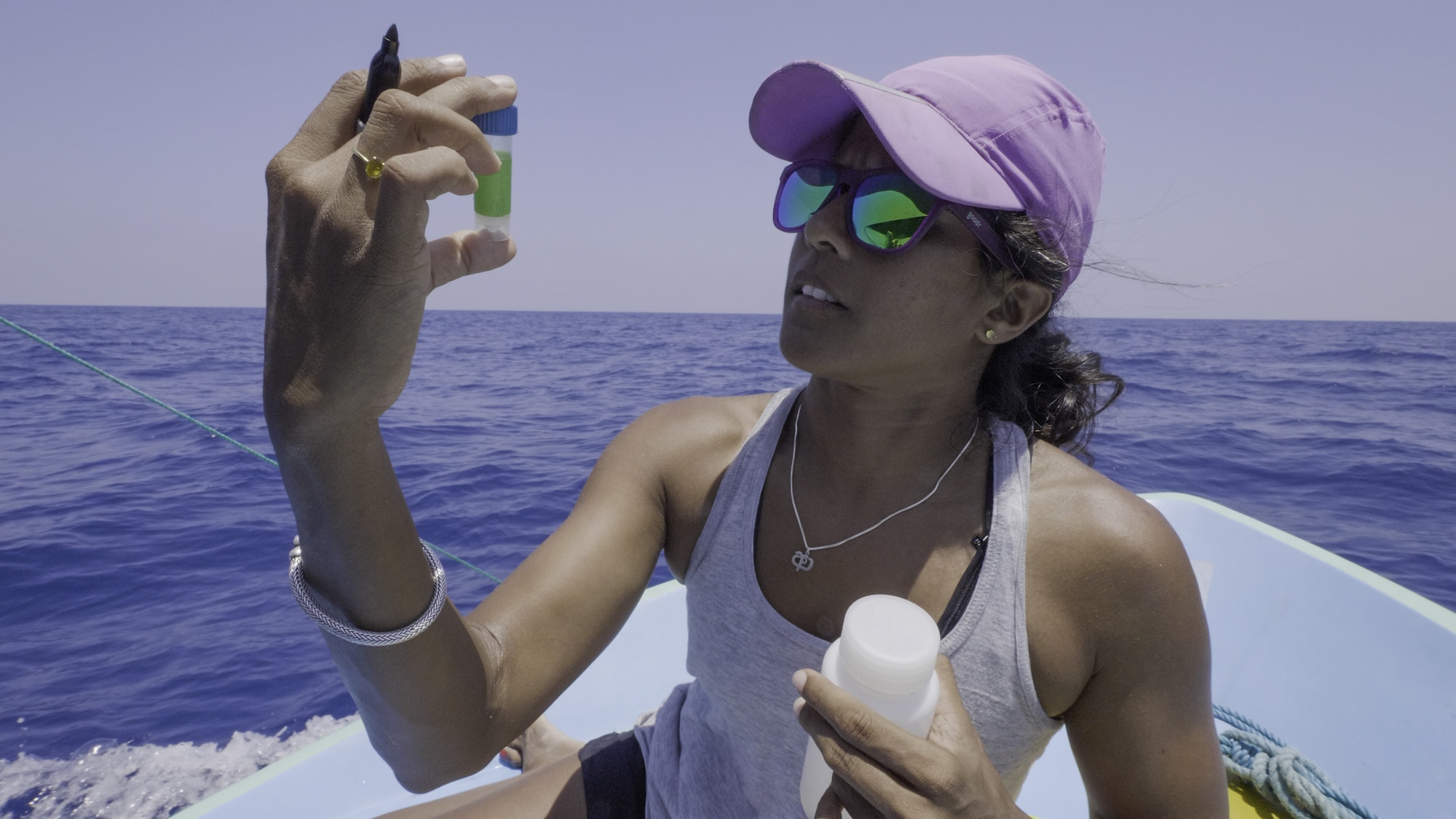 Marine biologist Asha DeVos studies a sample of sperm whale dung, which will give her clues into what the whales are eating. (National Geographic for Disney+/Andrew Mitchell)