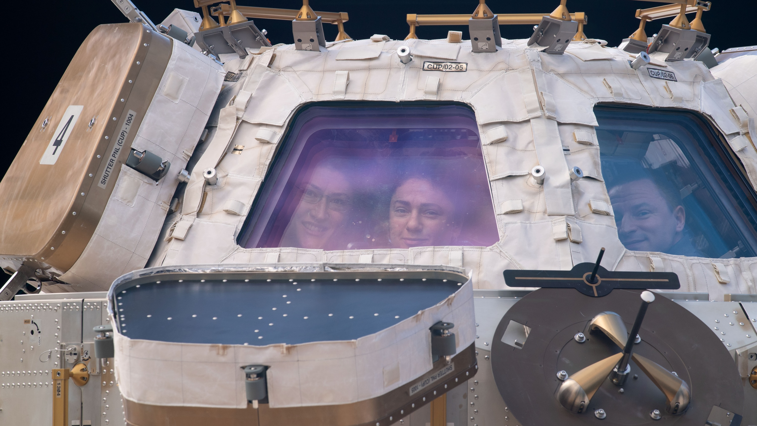 """AMONG THE STARS - (Nov. 4, 2019) - NASA astronauts (from left) Christina Koch, Jessica Meir and Andrew Morgan peer through the International Space Station's """"window to the world,"""" the cupola. The trio were on robotics duty monitoring the arrival and capture of the Cygnus space freighter from Northrop Grumman. (NASA) CHRISTINA KOCH, JESSICA MEIR, ANDREW MORGAN"""