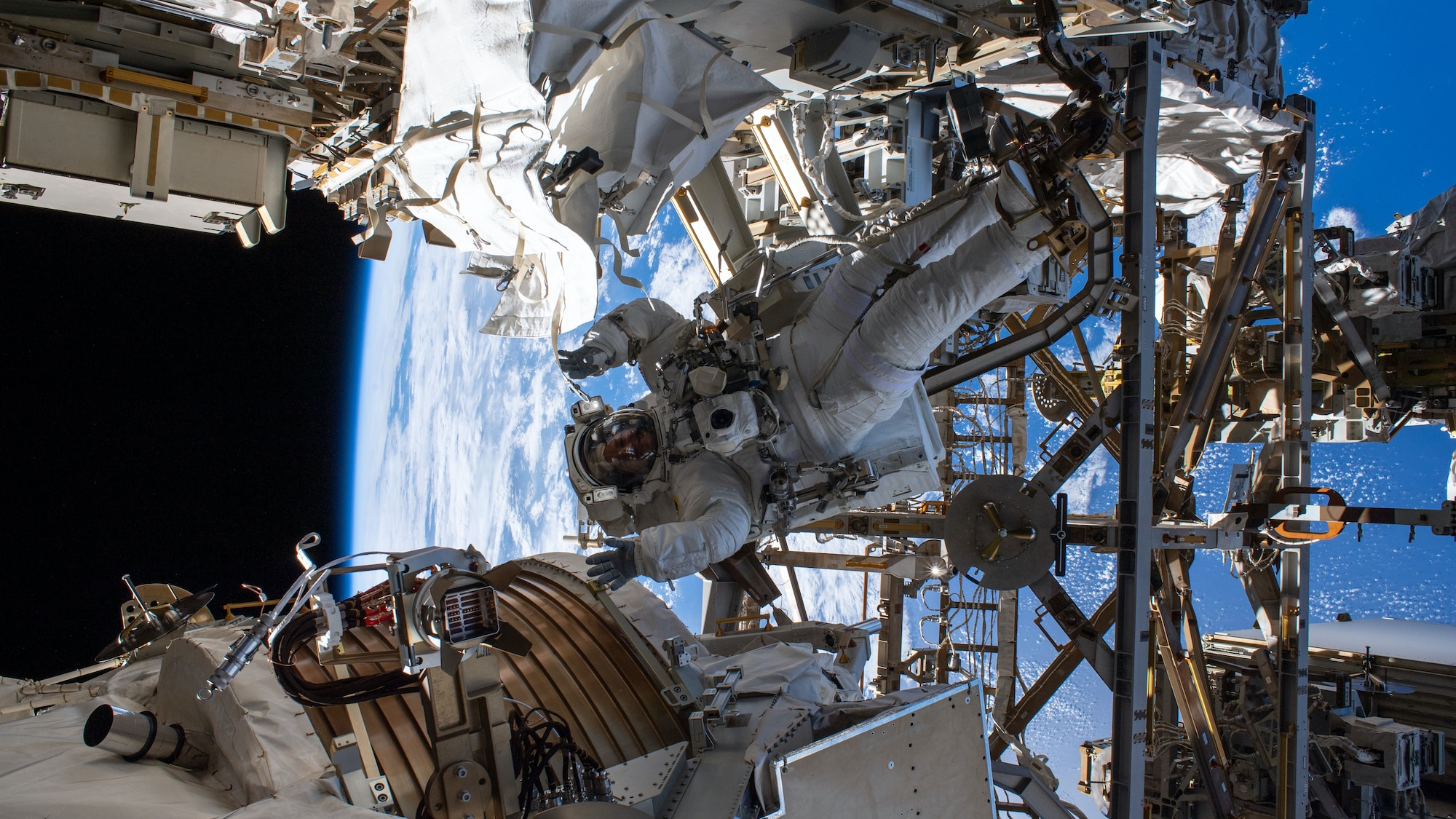 AMONG THE STARS - (Nov. 15, 2019) - NASA astronaut Andrew Morgan waves as he is photographed seemingly camouflaged among the Alpha Magnetic Spectrometer (lower left) and other International Space Station hardware during the first spacewalk to repair the cosmic particle detector. (NASA) ANDREW MORGAN