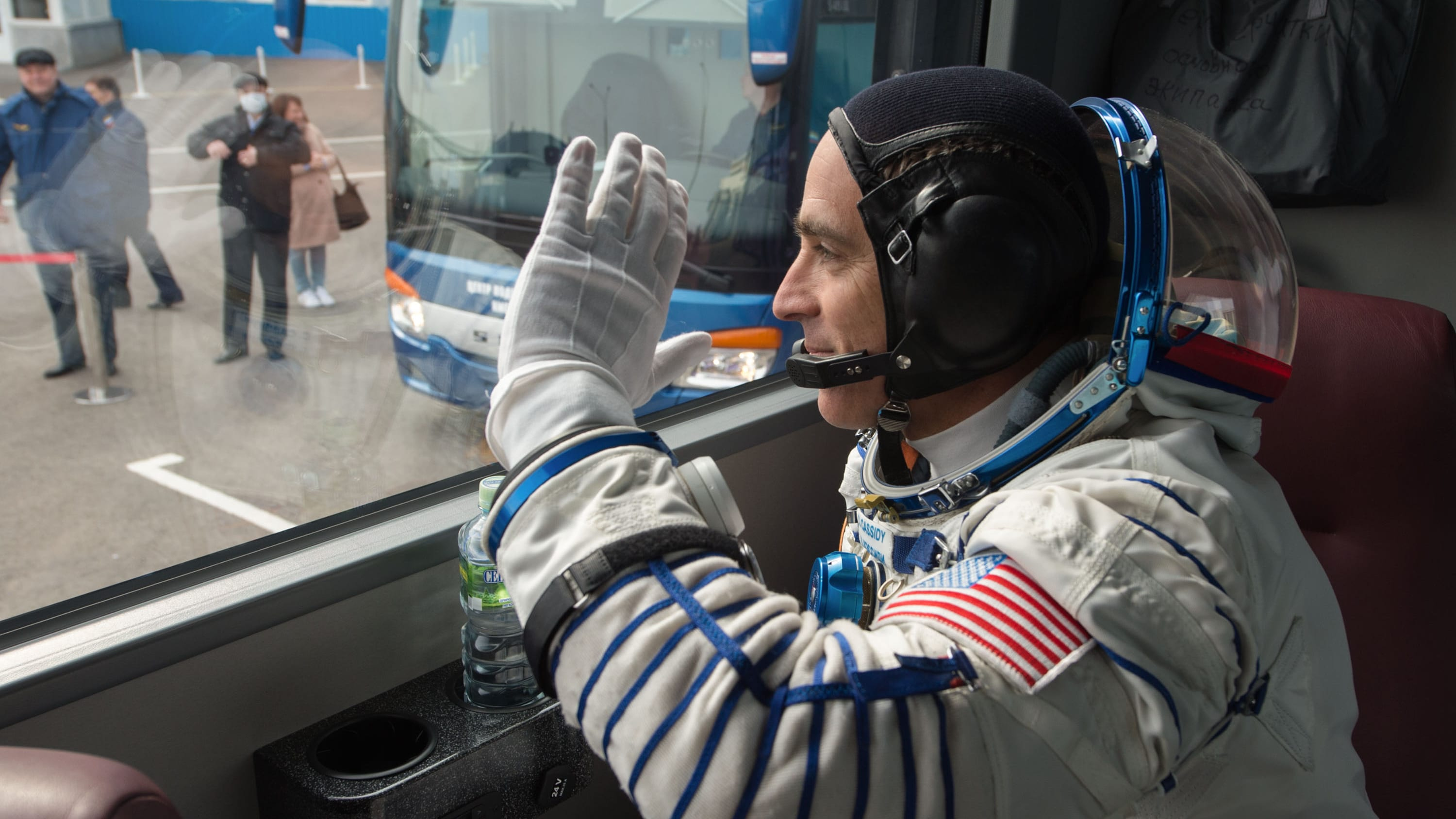 AMONG THE STARS - Expedition 63 crewmember Chris Cassidy of NASA waves farewell as he, Anatoly Ivanishin, and Ivan Vagner of Roscosmos depart building 254 via bus for the launch pad, Thursday, April 9, 2020 at the Baikonur Cosmodrome in Kazakhstan. A few hours later, they lifted off on a Soyuz rocket for a six-and-a-half month mission on the International Space Station. (NASA/GCTC/Andrey Shelepin) CHRIS CASSIDY