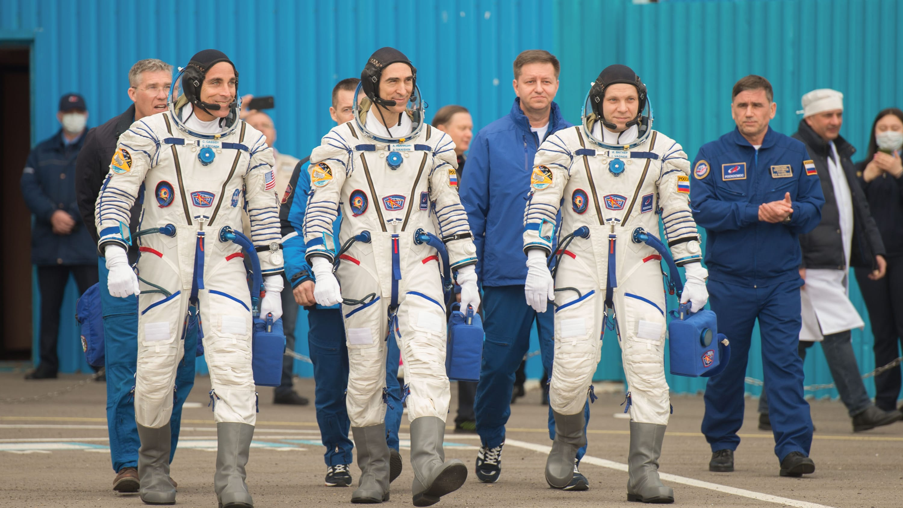 AMONG THE STARS - Expedition 63 crewmembers Chris Cassidy of NASA, left, Anatoly Ivanishin, center, and Ivan Vagner of Roscosmos, depart building 254 for the launch pad, Thursday, April 9, 2020 at the Baikonur Cosmodrome in Kazakhstan. A few hours later, they lifted off on a Soyuz rocket for a six-and-a-half month mission on the International Space Station. (NASA/GCTC/Andrey Shelepin) CHRIS CASSIDY, ANATOLY IVANISHIN, IVAN VAGNER