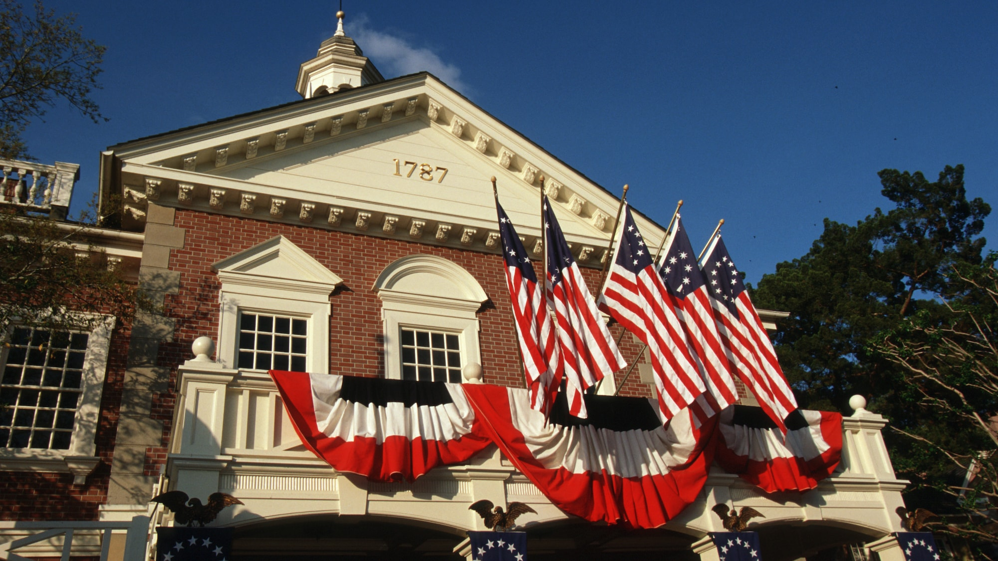 Image of The Hall of Presidents building exterior displaying American flags.