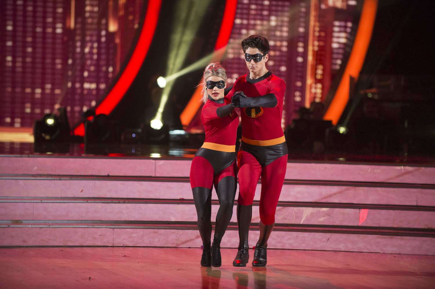 Milo Manheim and Witney Carson dancing in matching Incredibles-inspired super suits