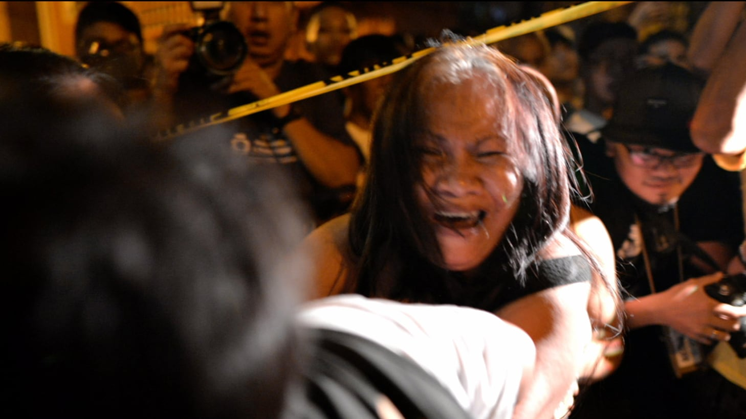 A woman fights with a police officer at a crime scene in Manila. (Photo by Ezra Acayan)
