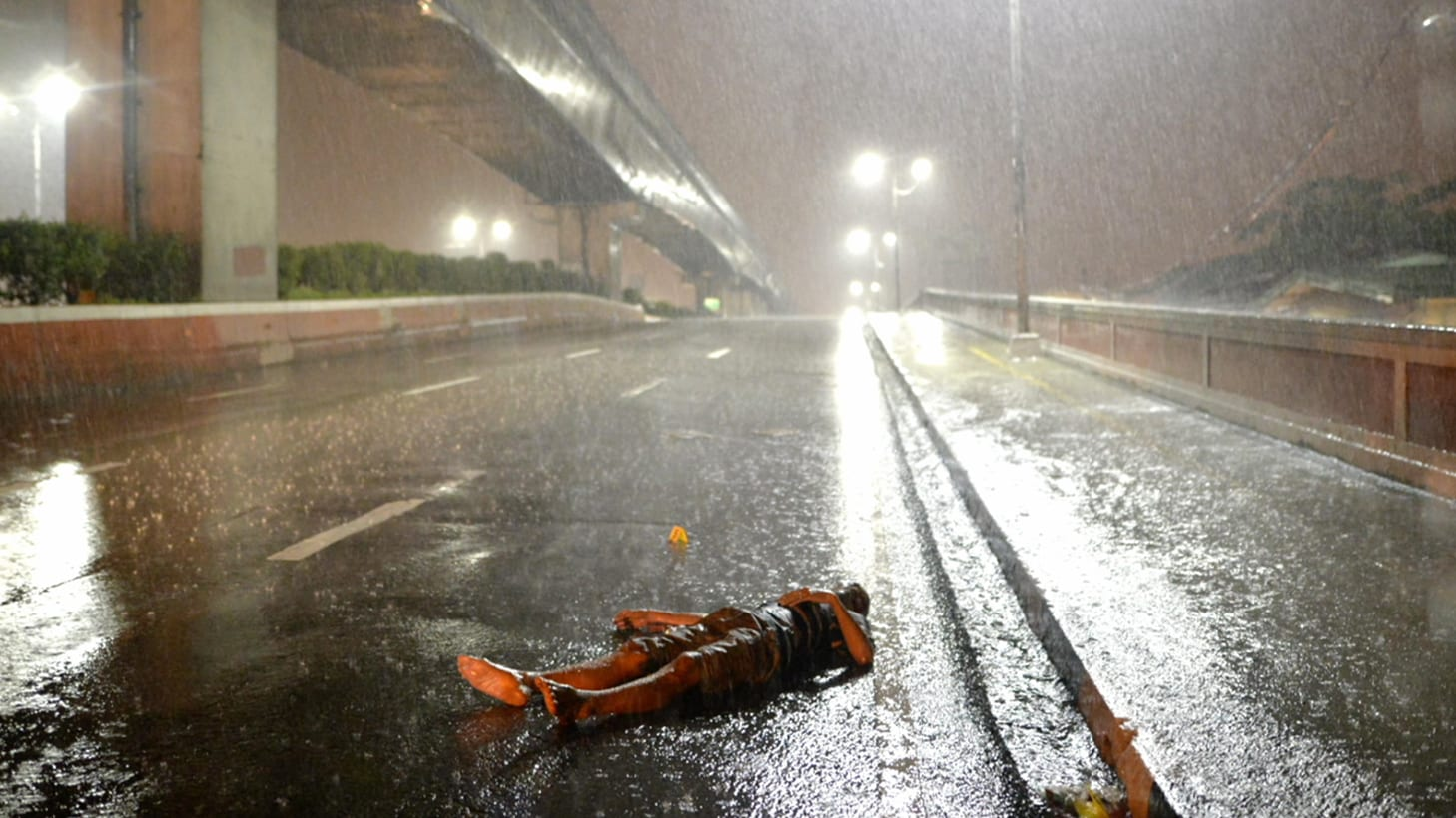 A body lies on a Manila highway in the rain. (Photo by Ezra Acayan)