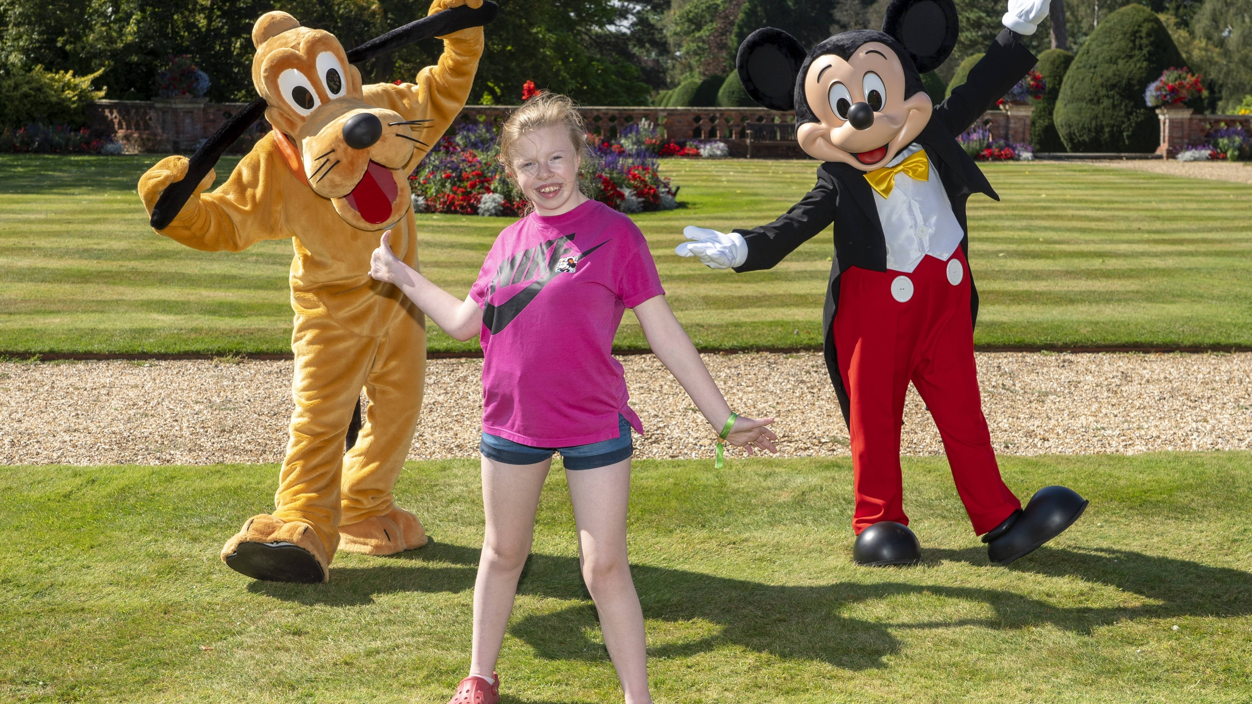 Girl posing with Mickey and Pluto