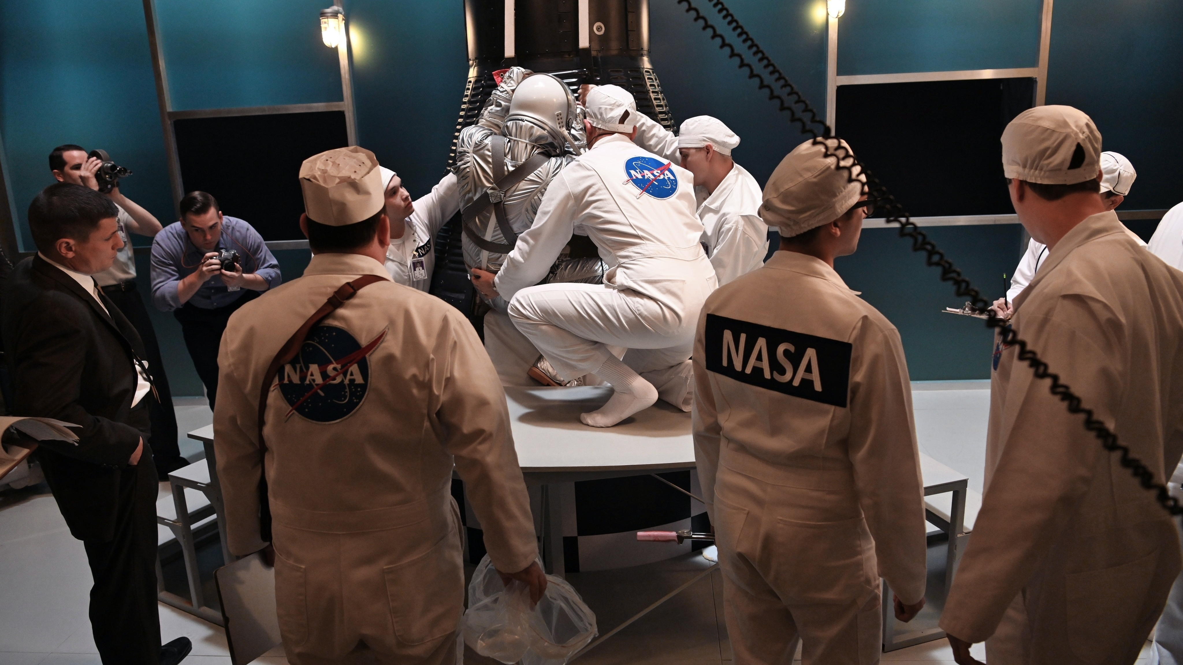 Alan Shepard (standing left)  played by Jake McDorman prepares to enter the Mercury capsule with the assistance of John Glenn (center) played by Patrick J. Adams in National Geographic's THE RIGHT STUFF streaming on Disney+. (Credit: National Geographic/Gene Page)