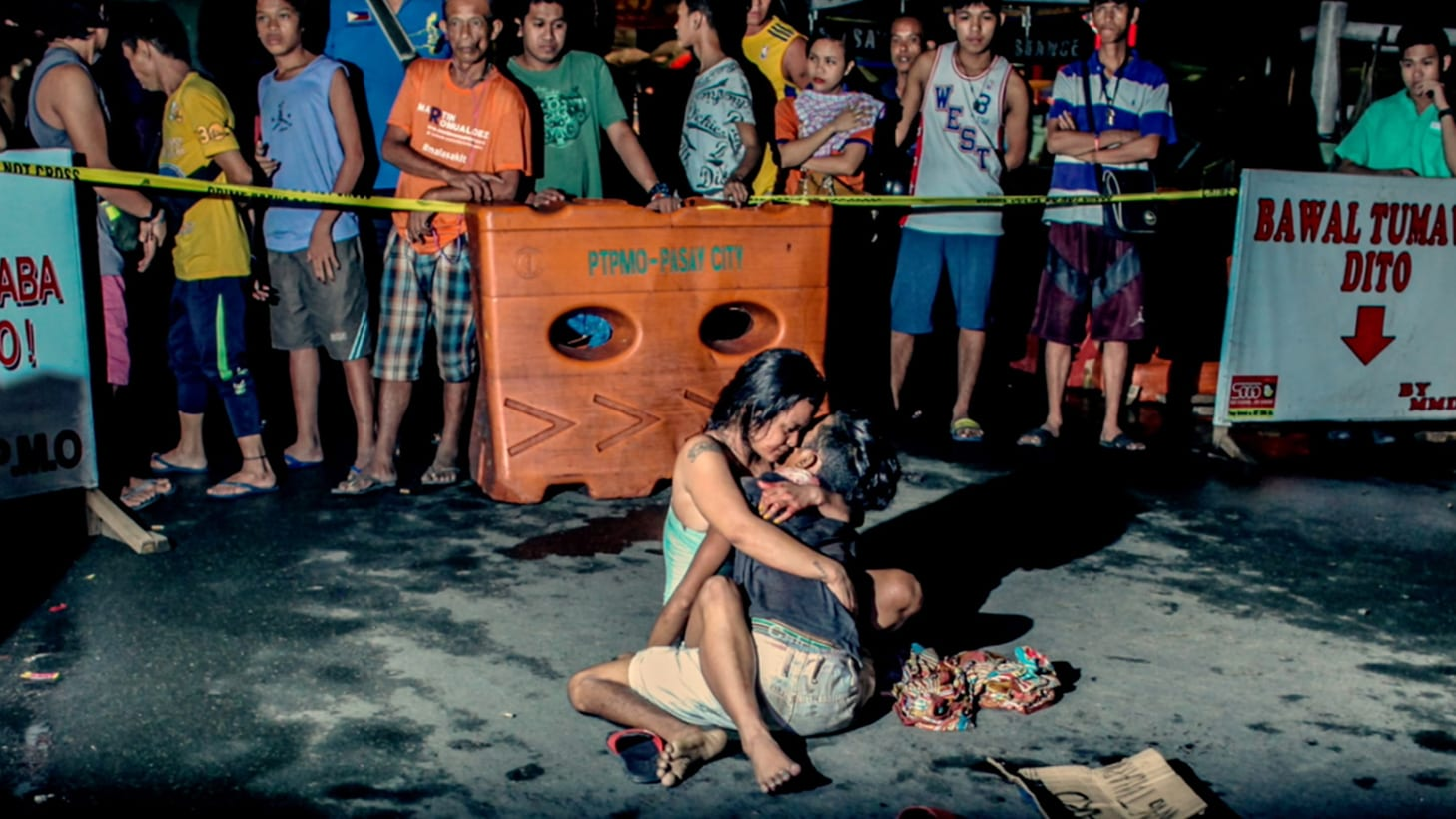 A woman cradles the lifeless body of her partner at a crime scene in Manila. (Photo by Basilio Sepe)