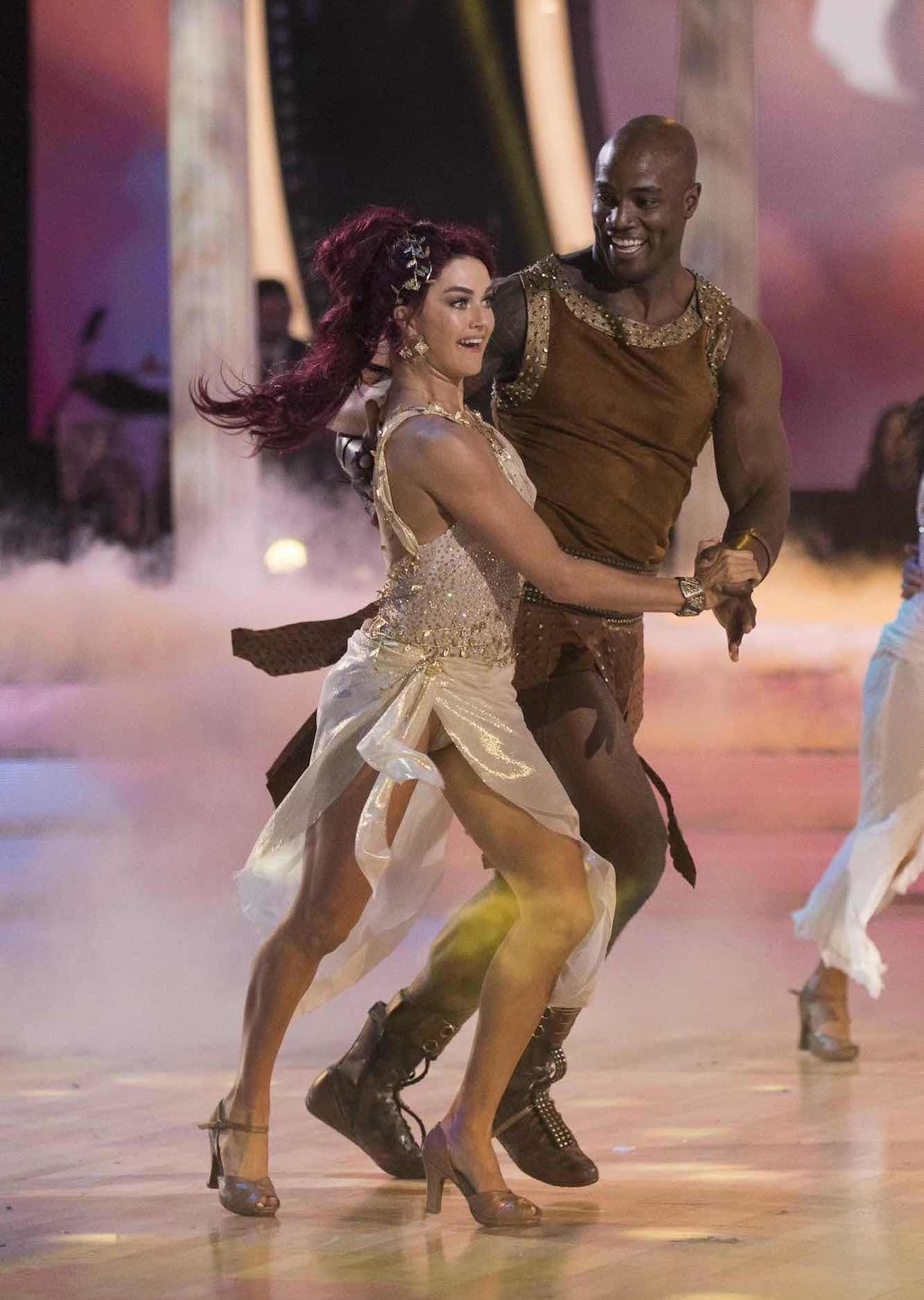 DeMarcus Ware and Lindsay Arnold dancing, dressed as characters from Hercules