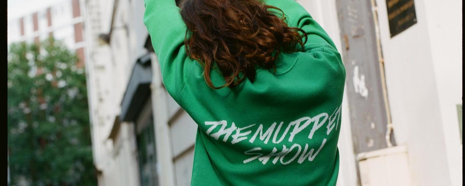 "Model wearing green sweatshirt with text ""The Muppet Show"" from the Sandro collection"