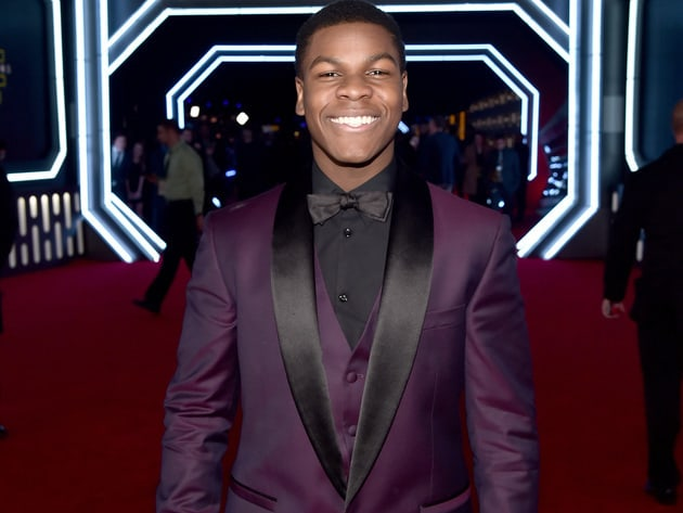 A smiley John Boyega, Finn in the movie, poses on the red carpet. Boyega wore one leather glove o...