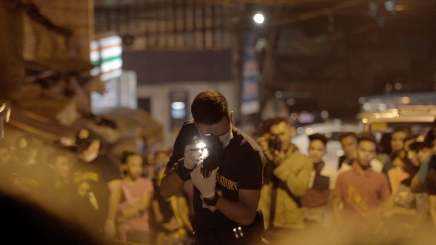 A Manila police officer takes a photo at a crime scene while a crowd watches in the background. (Genius Loki Film and Violet Films/Alexander A. Mora)