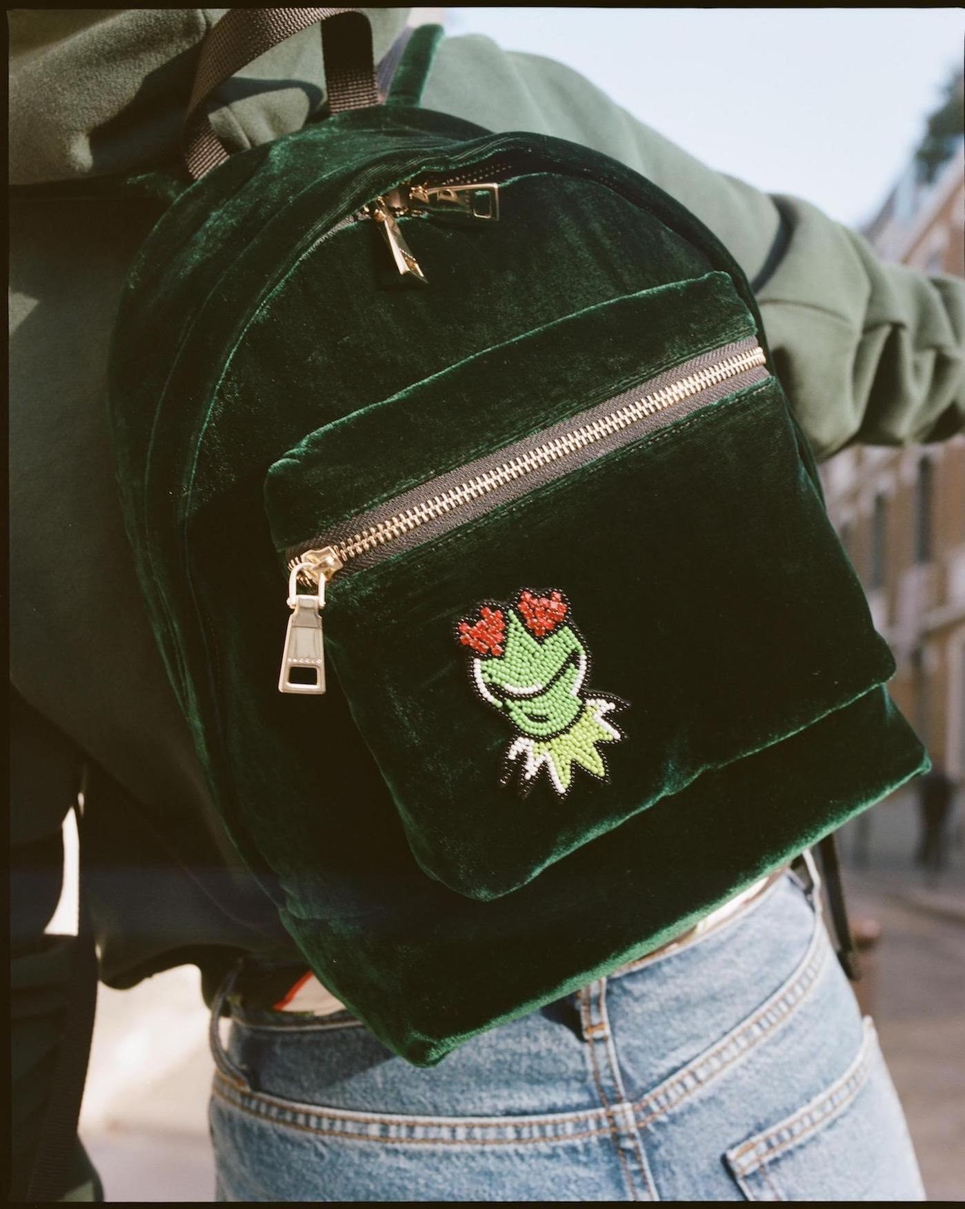 Model wearing a velvety green back pack featuring Kermit from the Sandro collection