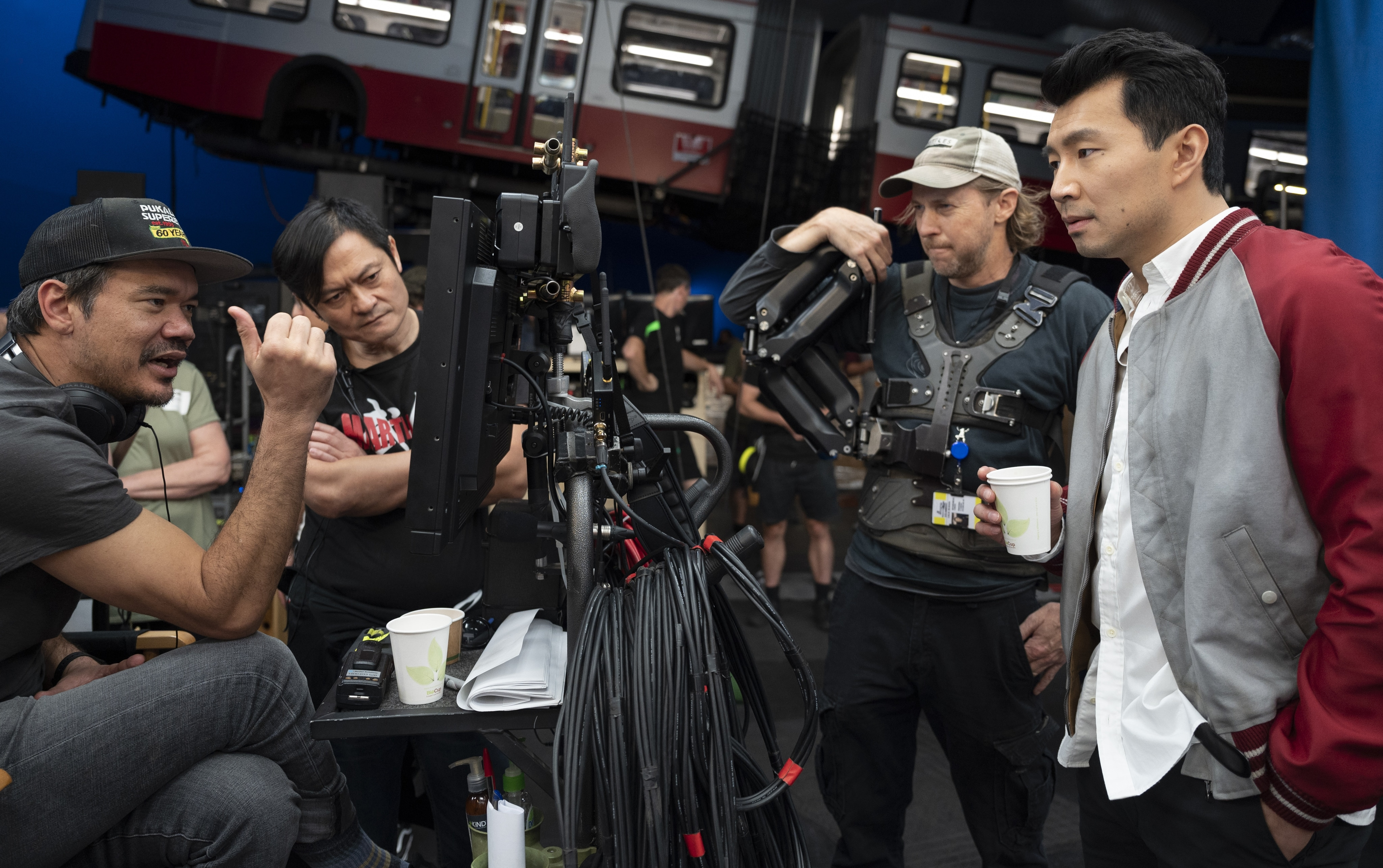Director Destin Daniel Cretton looks at the monitor and chats with his team, including actor Simu Liu, on set.