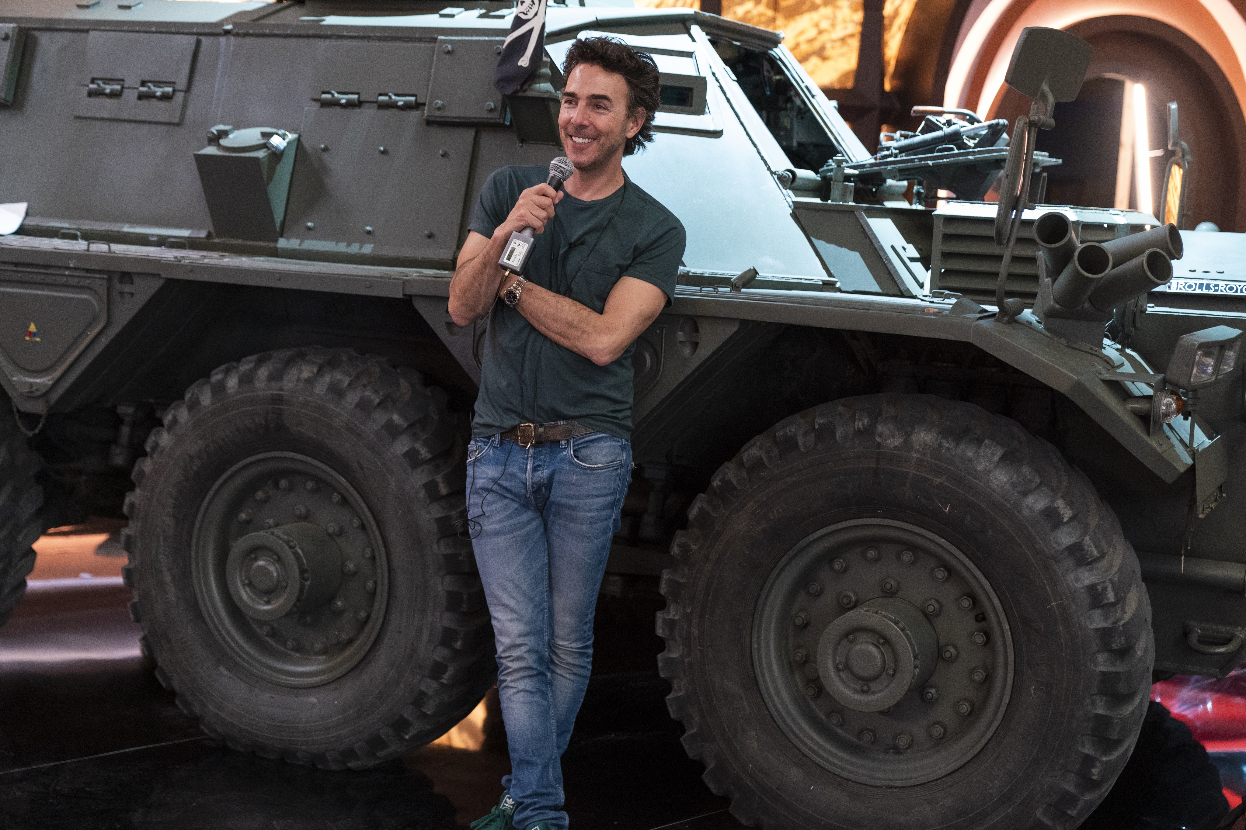 Free Guy Director Shawn Levy leans up against a large car on set