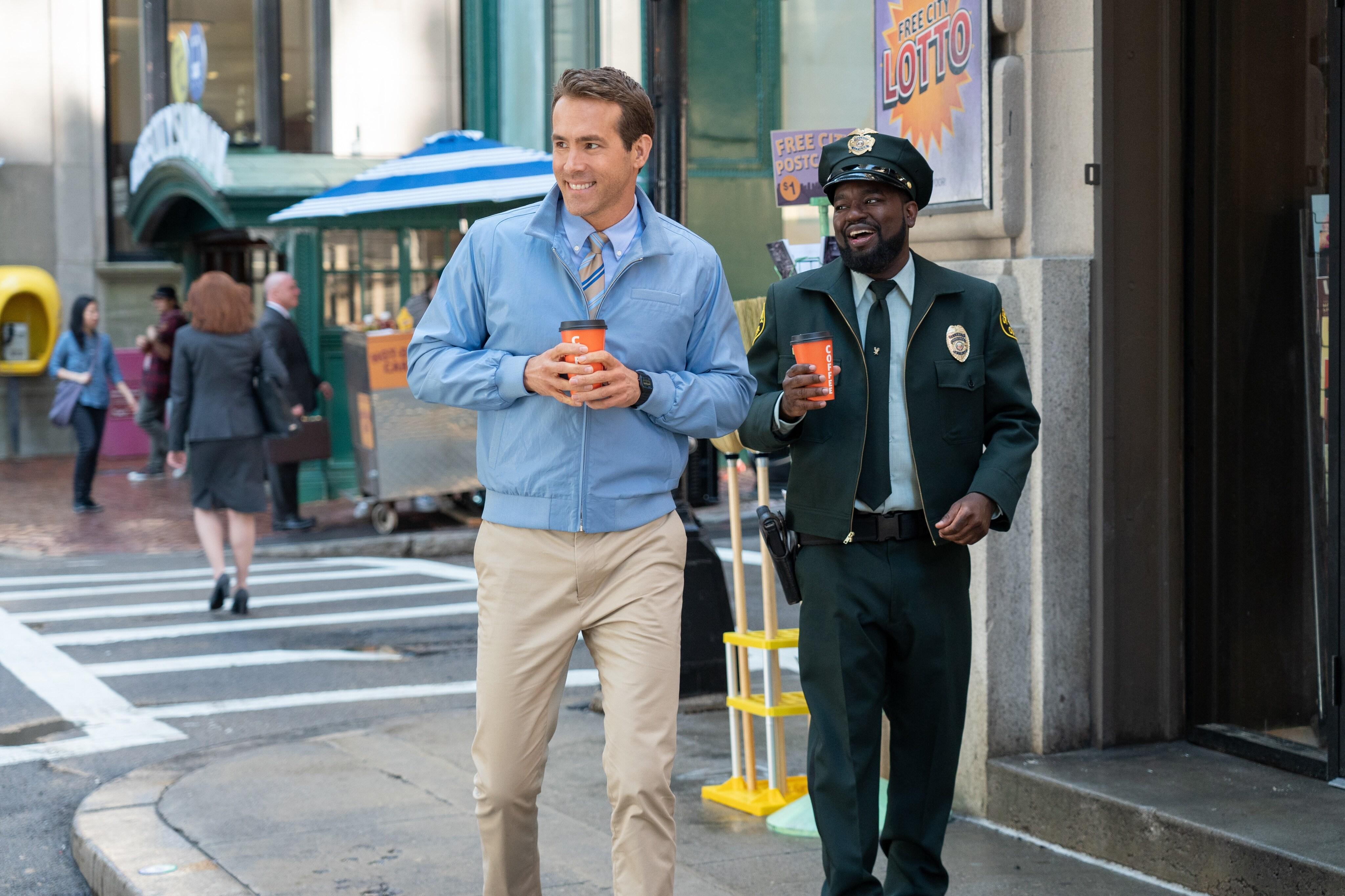 Ryan Reynolds walks down the street in a scene from Free Guy