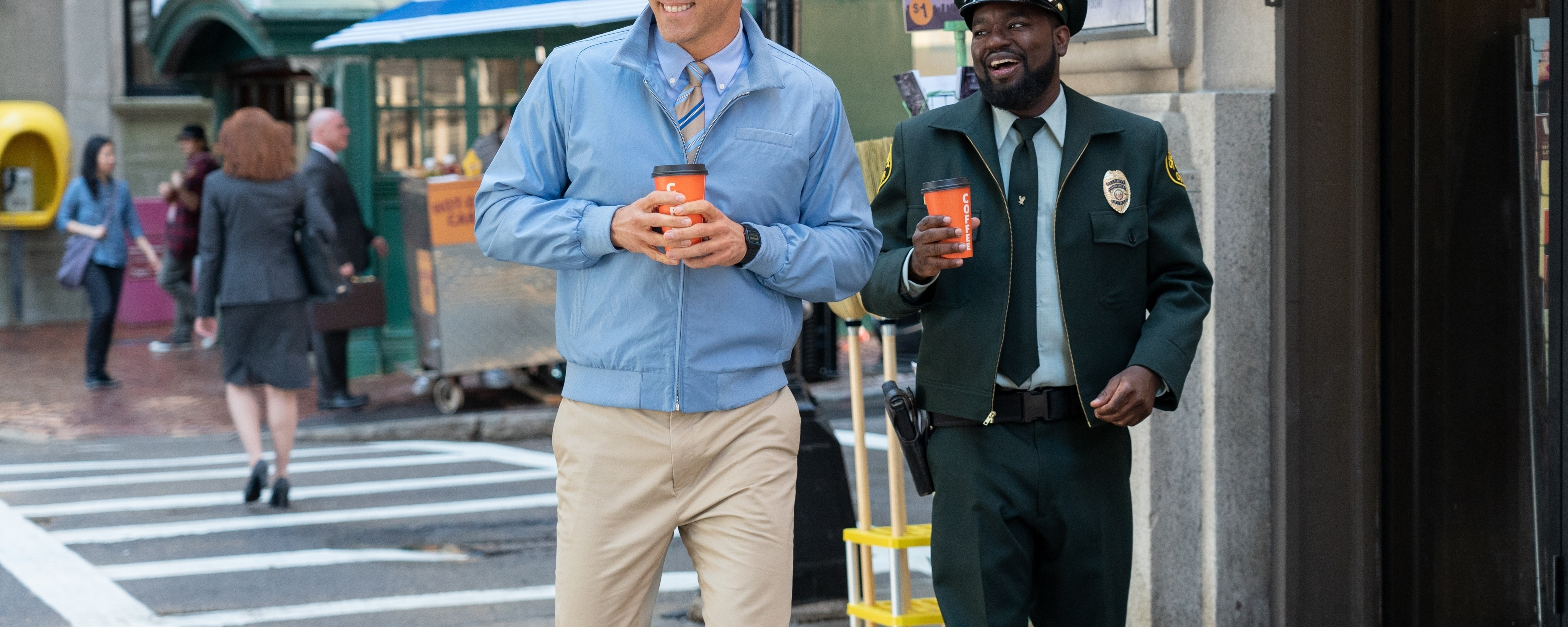 Ryan Reynolds and Lil Rel Howery walk down the street in a scene from Free Guy