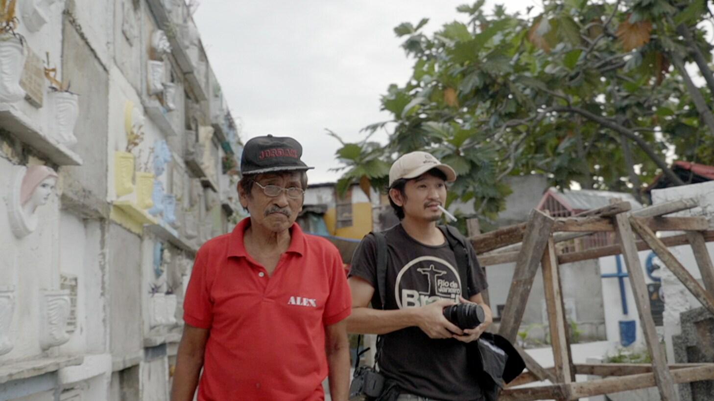 Raffy Lerma walks with a man through a graveyard in Manila. (Genius Loki Film and Violet Films/Alexander A. Mora)