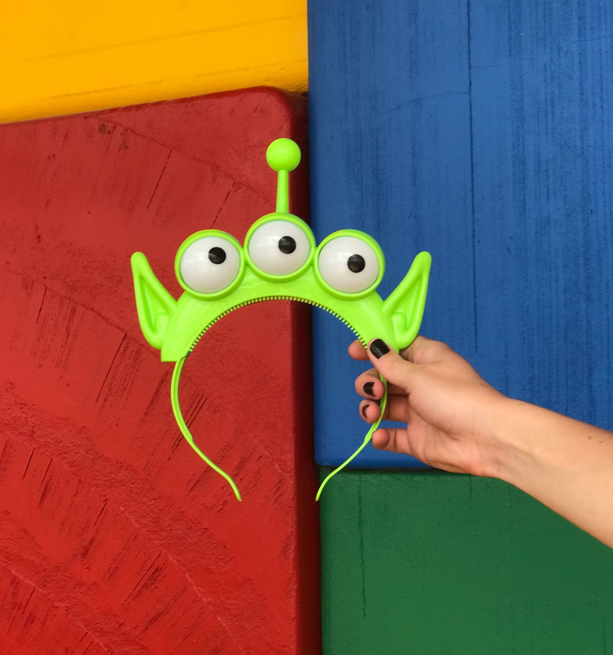 Alien Headband in front of block wall at Toy Story Land in Walt Disney World