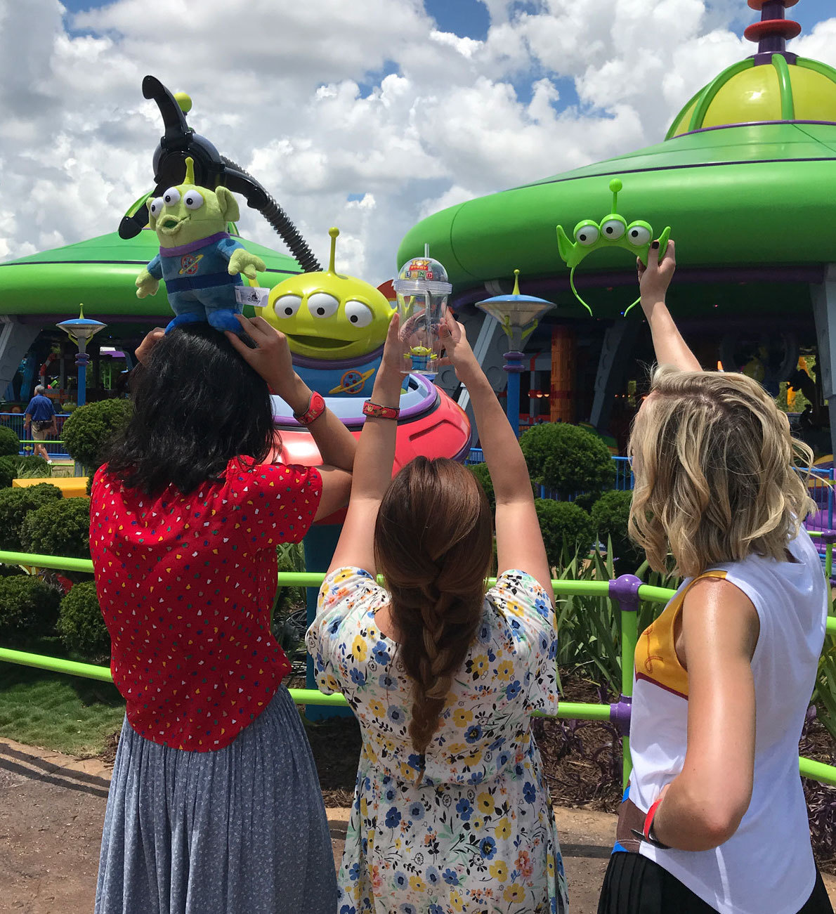 Correspondents Holding up alien merchandise in front of Alien Swirling Saucers in Toy Story Land in Walt Disney World