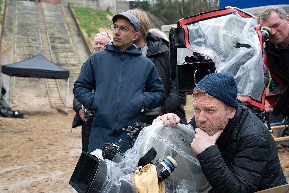 Director Kenneth Branagh with cinematographer Haris Zambarloukos in front of crew on the set outside