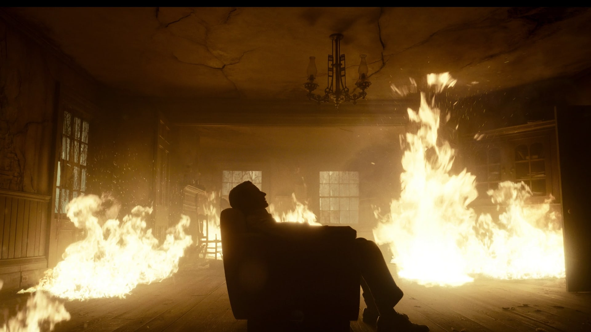 A man sits in a burning room from the movie Nightmare Alley
