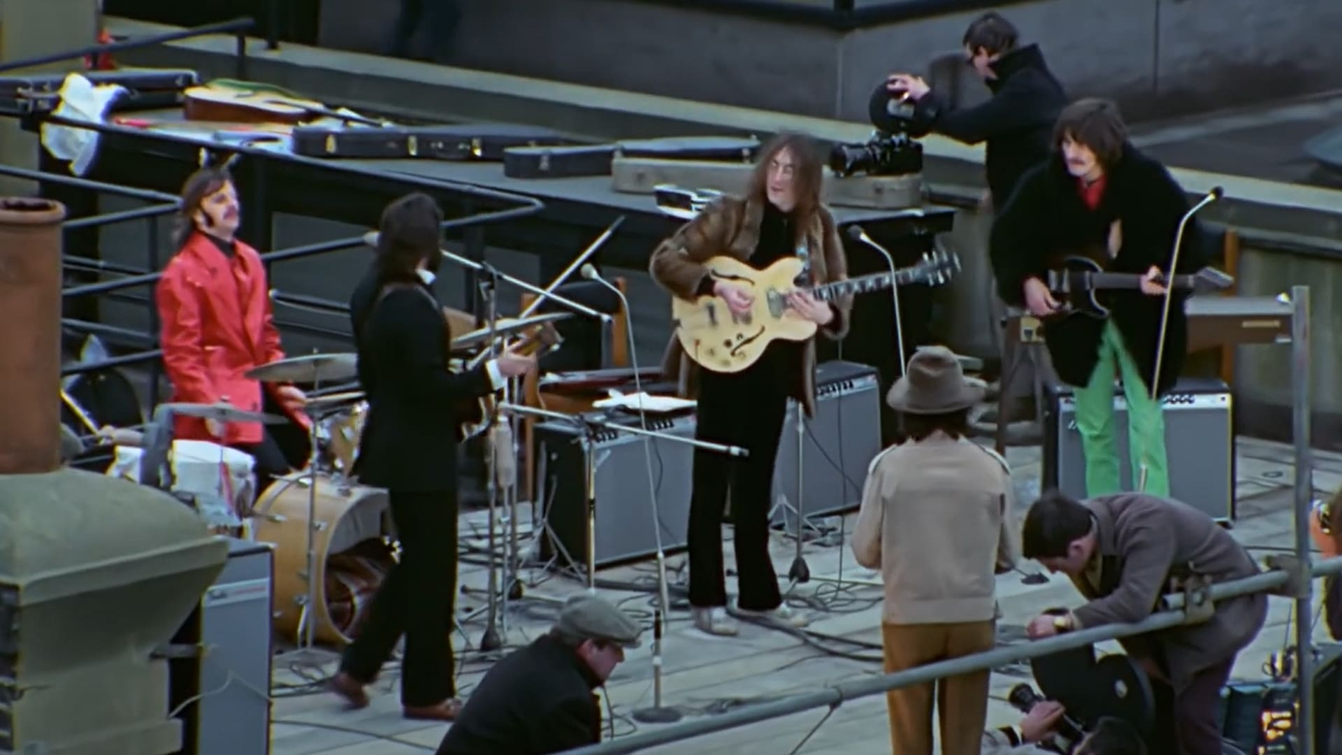 The Beatles perform on a city rooftop surrounded by a film crew