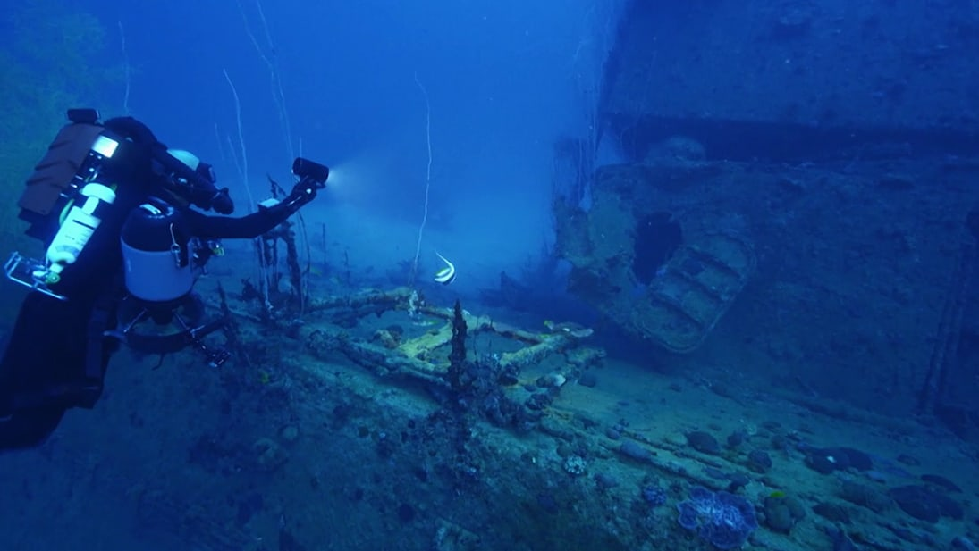 A diver swims near underwater shipwreck from National Geographic's Ocean Wreck Investigation