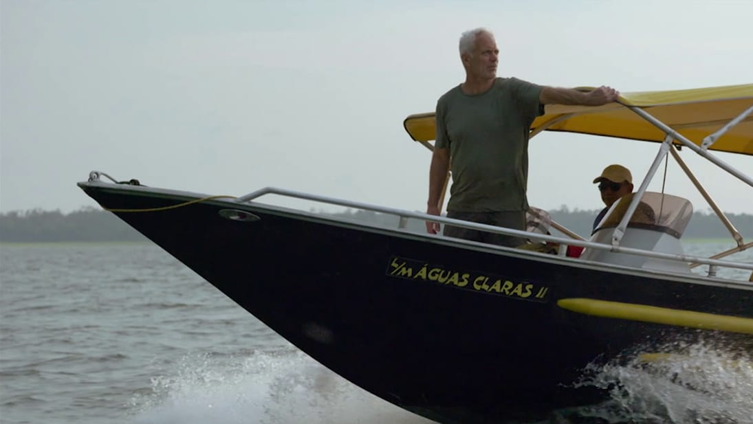 Jeremy Wade stands on the bow of a boat as it travels through water from National Geographic's Unknown Waters with Jeremy Wade