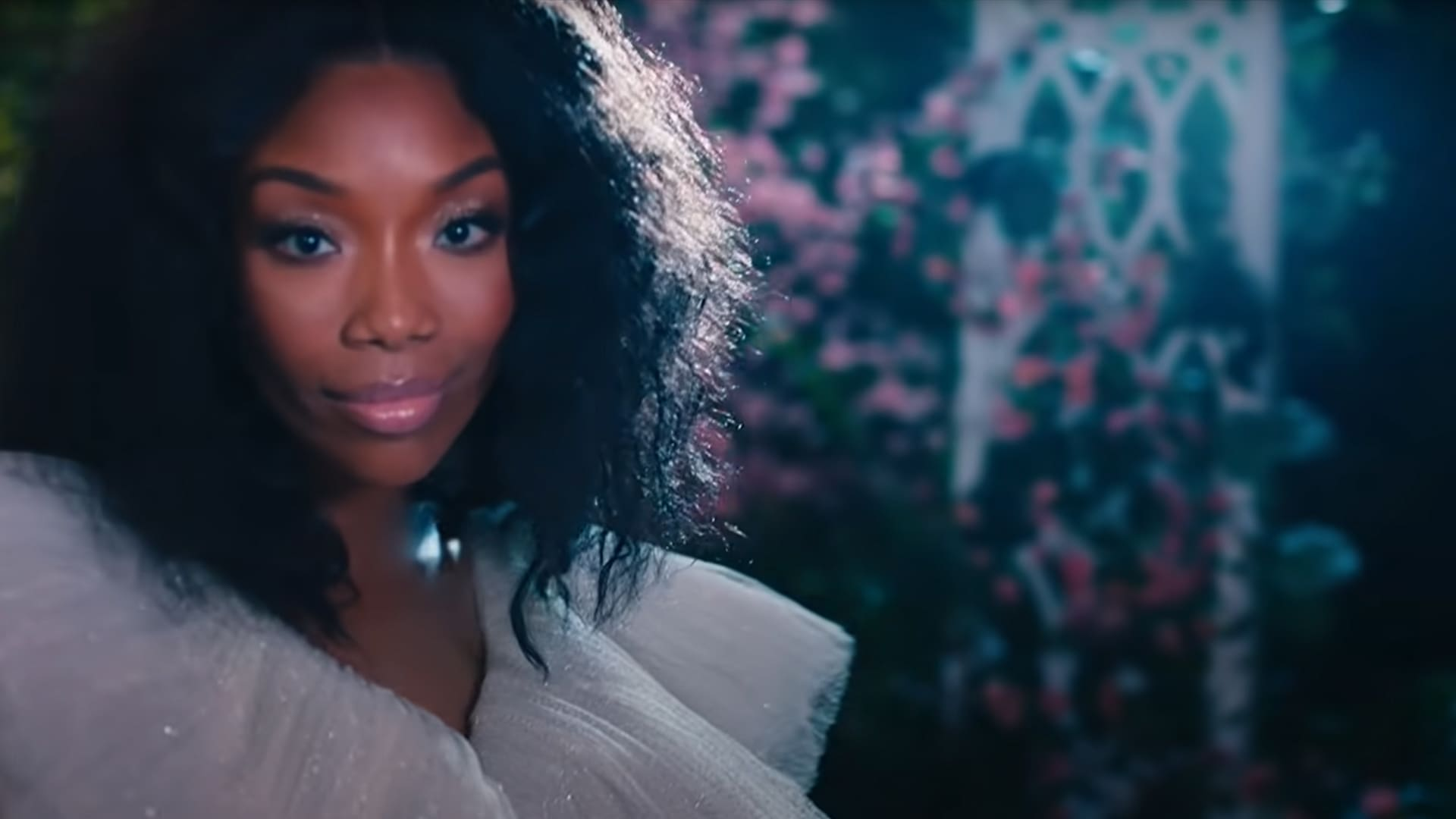 Brandy stands in front of flowers from the Starting Now official music video