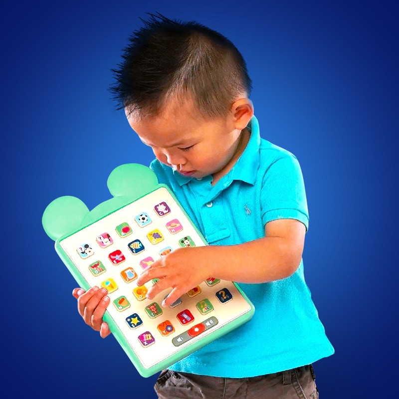 A young boy plays with a tablet toy from the Disney Hooyay range on a dark blue background
