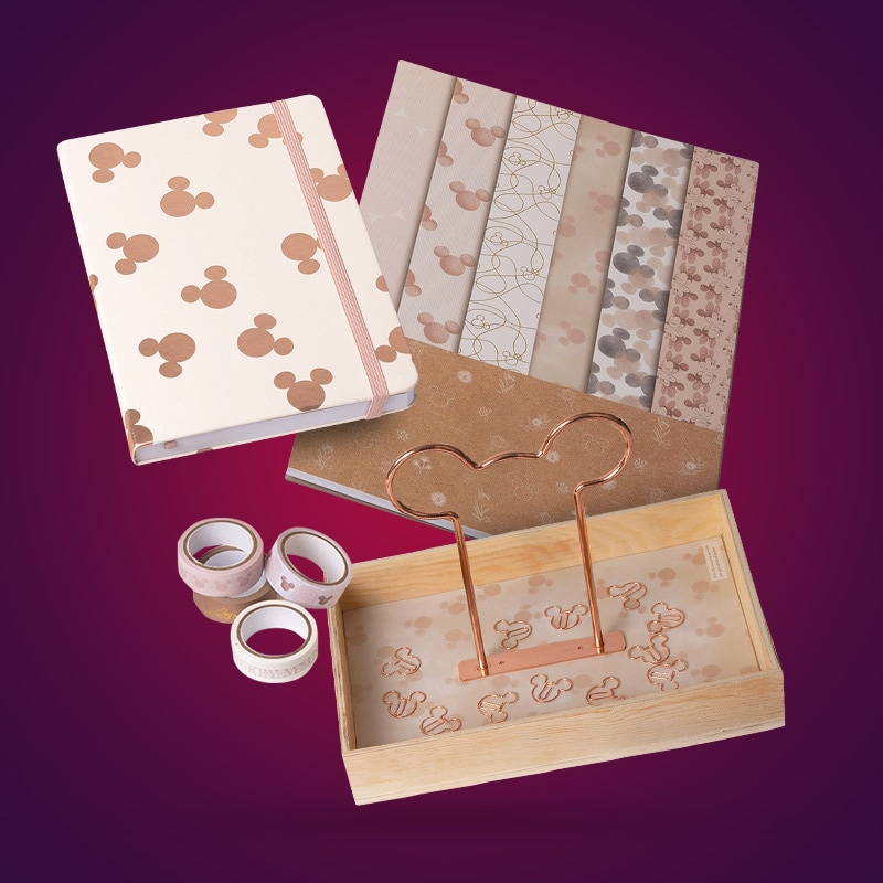 A collection of Mickey Mouse stationery items and desk accessories on a maroon background