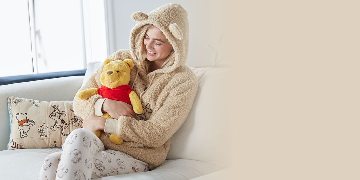 A woman wears Winnie The Pooh sleepwear and cuddles a Winnie The Pooh plush toy from shopDisney UK