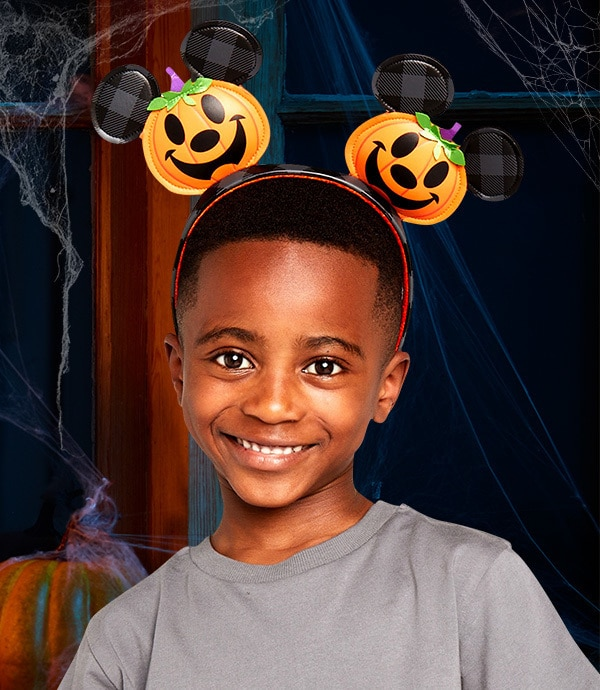 A young boy wears a jack-o'-lantern headband from shopDisney UK's Halloween collection