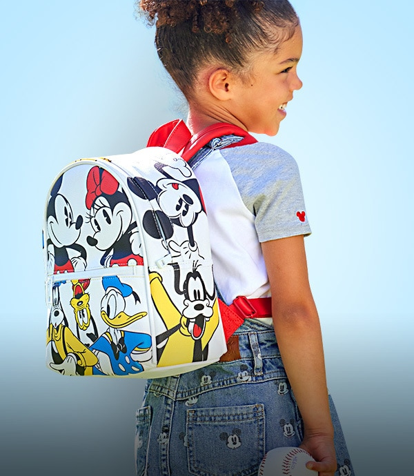 A young girl with a backpack from the Mickey Baseball Collection available on shopDisney.