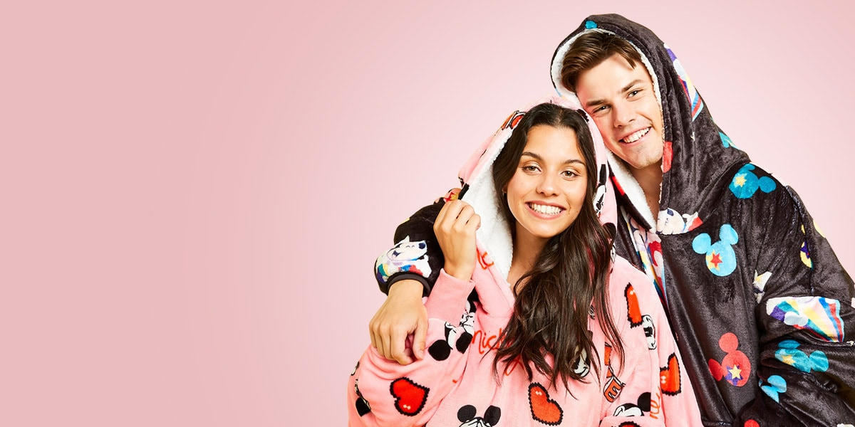 A couple wearing the Disney range of Oodie wearable blankets