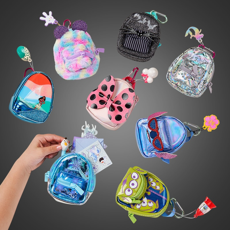 A collection of Disney and Pixar-themed Real Littles backpacks on a dark grey background