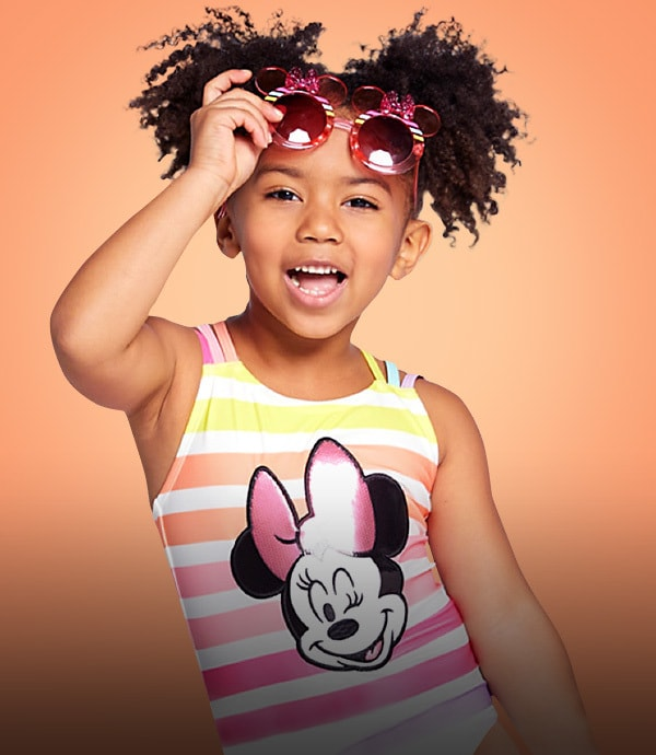 A young girl wearing sunglasses and a Minnie Mouse swimming costume on an orange background.