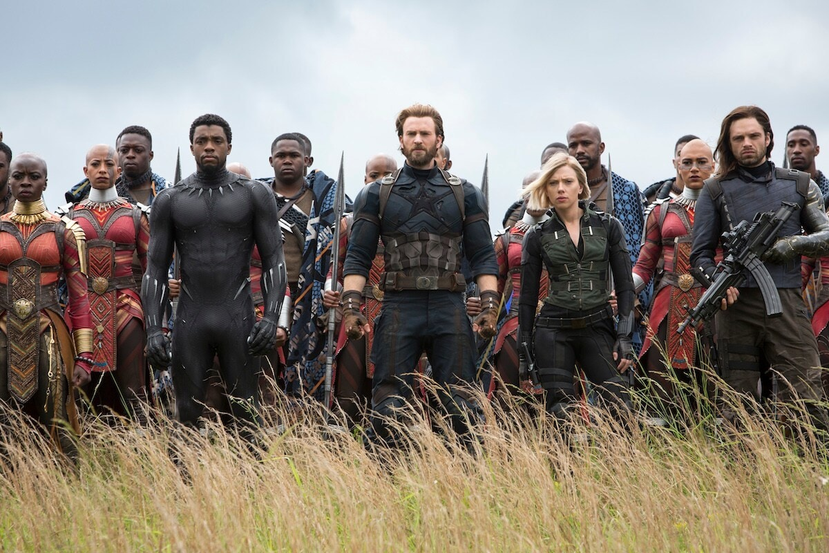 Black Panther, Captain American, Black Widow and the Winter Soldier all stand together in a grassy field in a scene from the movie Avengers: Infinity War.