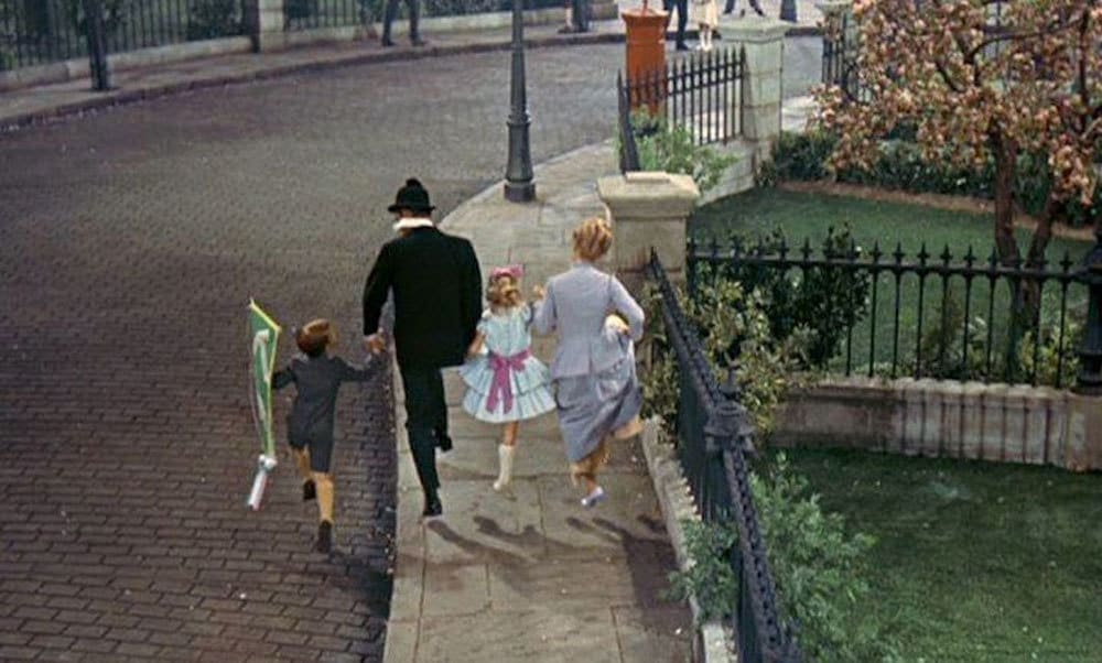The Banks family skipping along the sidewalk.