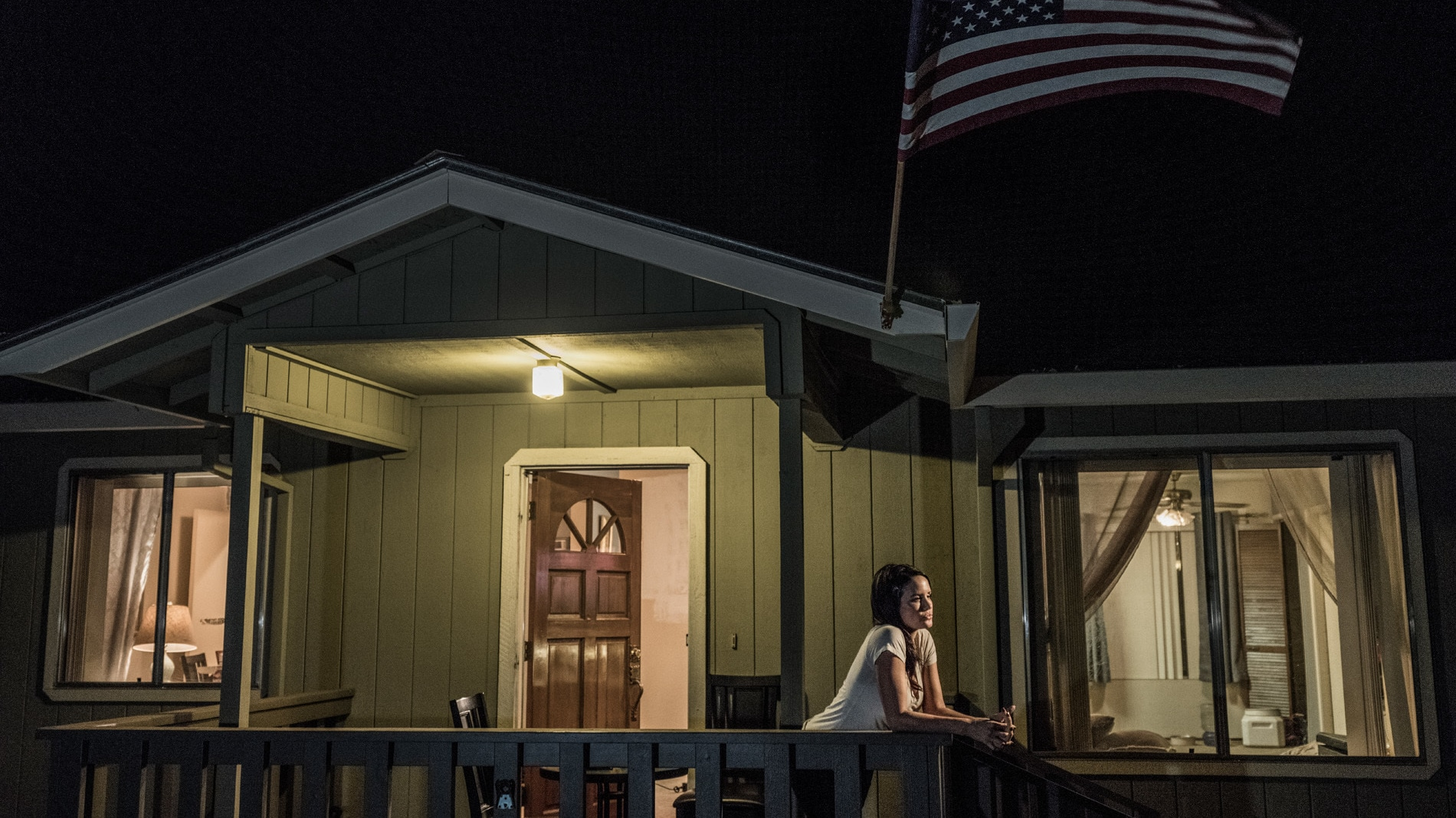 Carly Ingersoll leans on the edge of the porch of her home in Paradise, CA. (National Geographic/Pete Muller)