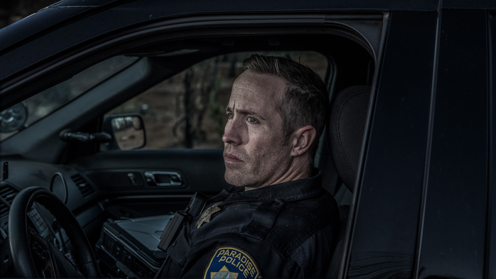 Officer Matt Gates sits for a portrait in the burned out area in Paradise, CA, to which he often responded to distress calls. (National Geographic/Pete Muller)