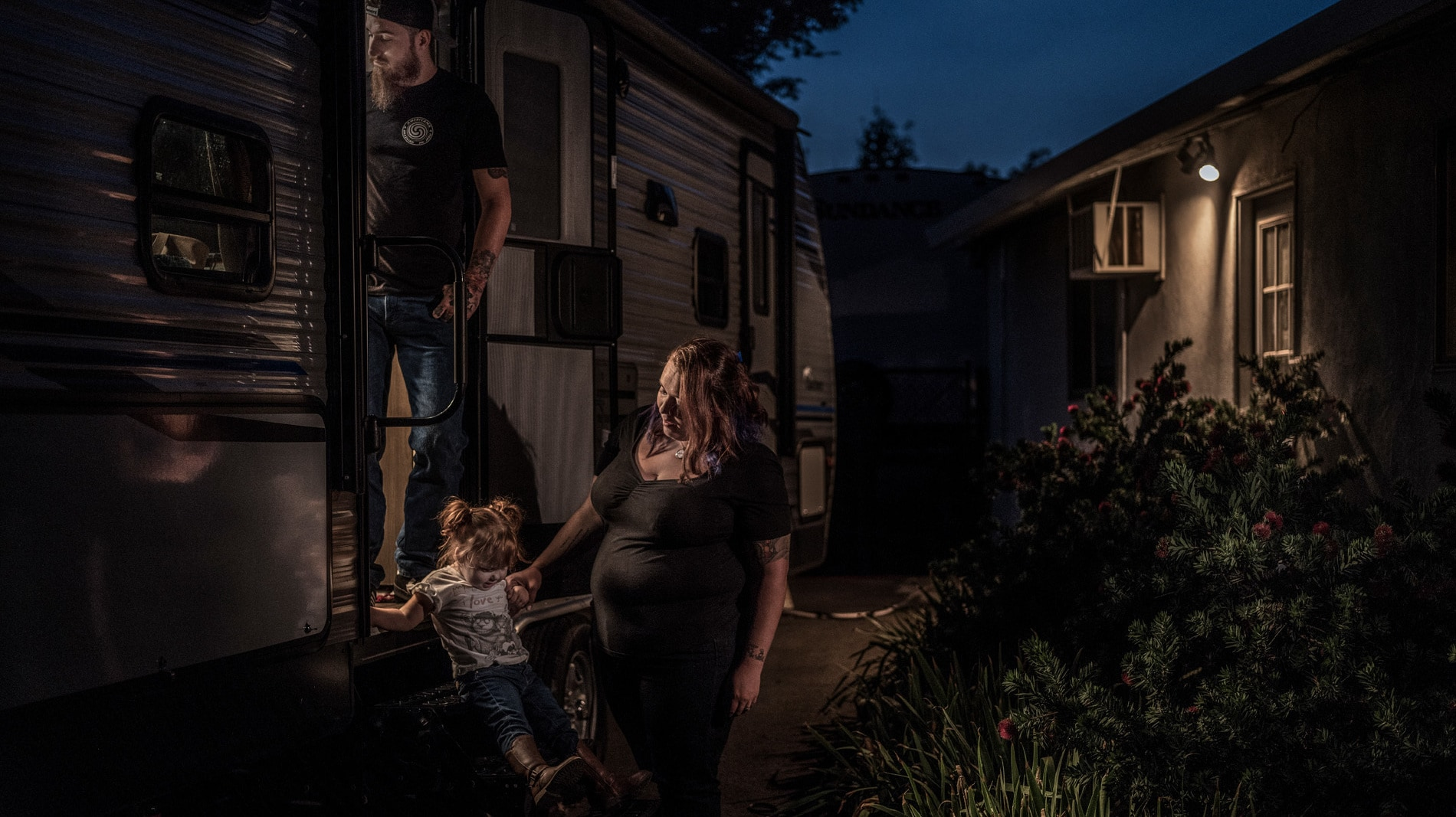 Justin, Kayla and Amberley Cox on the steps of their trailer in Paradise, CA. (National Geographic/Pete Muller)