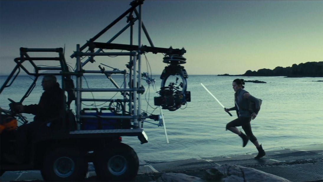 Rey running next to the water behind a car with cameras for the shooting of Star Wars: The Last Jedi