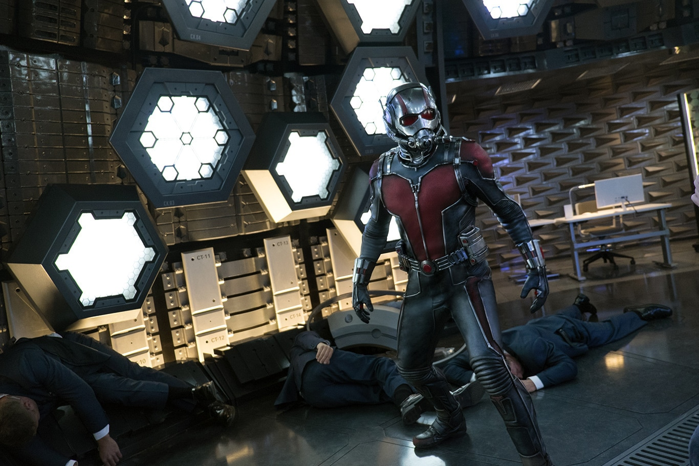 Ant-Man standing over unconscious men in suits in the movie Ant-Man