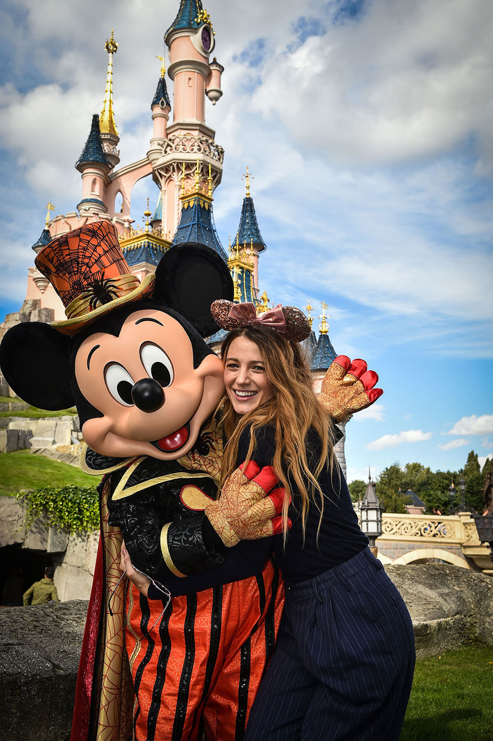Blake Lively hugging Mickey Mouse, posing for the camera